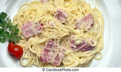 Pasta Carbonara on a white plate rotates in a circle