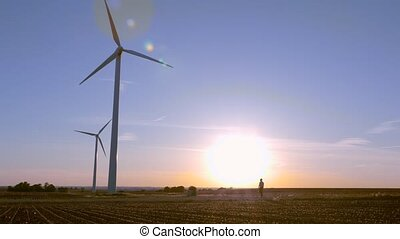 Engineer walks by the windmills at sunset