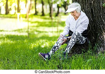 Serious old woman recreating after training in green forest...