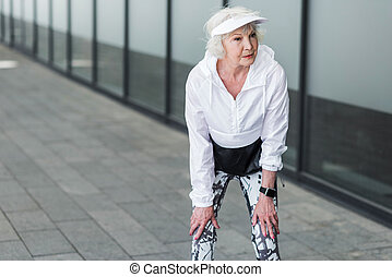 Sad elderly lady resting after physical drill near city building