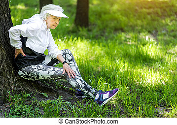 Tired old woman resting after strong training outdoors