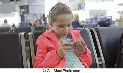 Little girl playing games on smartphone in airport hall -...