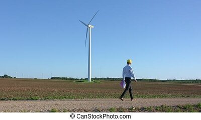 Engineer goes against the background of windmills