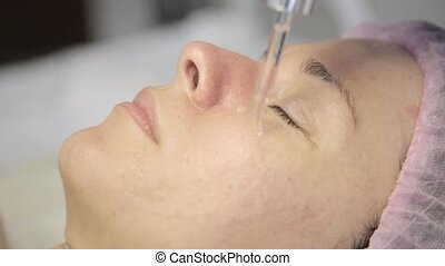 Close-up of beauty skin care. Cosmetologist applies an oil...