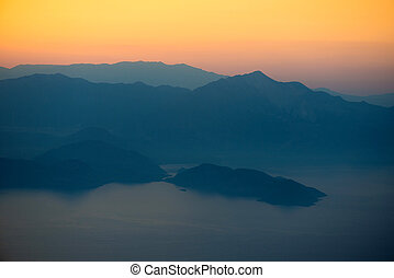 Orange sunset in the mountains. View from a height.