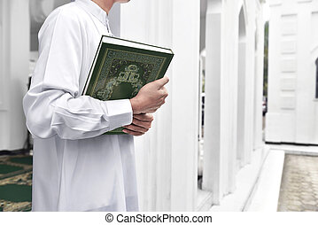 Muslim man hands holding the Koran