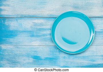 Top view of blue empty plate on blue wooden background with...