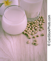 Fresh Soy milk (Soya milk) in a glass and soybean seeds -...