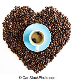 Heart of coffee beans with azure blue cup isolated on white background