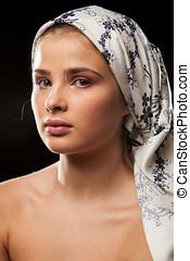 Portrait of beautiful woman wearing a headscarf on black...