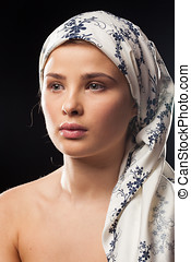 Portrait of young woman wearing a headscarf on black...