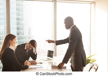 Angry african-american boss yelling at caucasian employees, scol