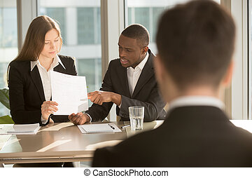 Multiracial employers making hiring decision, discussing resume,
