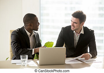 Two accomplished multiracial businessmen discussing business...