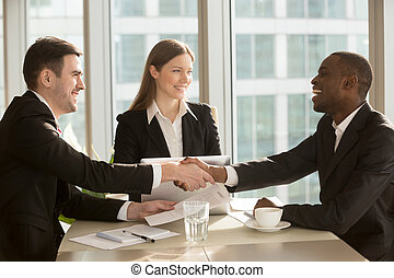 Happy smiling black and white businessmen handshaking after...