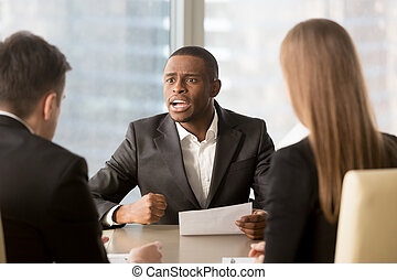 Dissatisfied african-american boss clenching fist, scolding empl