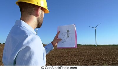 Engineer looks at the windmill drawings on the background of...