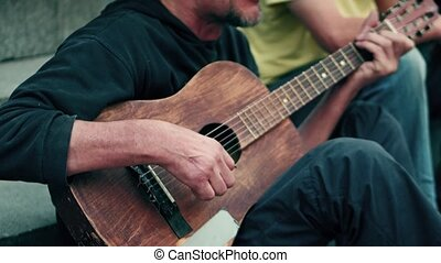 Unidentified mid aged street musician playing the guitar and...