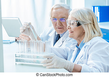 Smiling senior chemists working with test tubes in laboratory