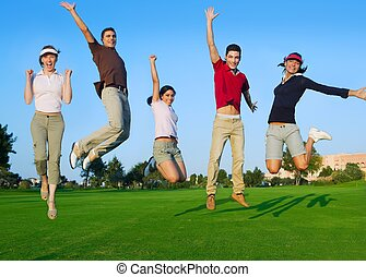 group of young people jumping outdoors grass - happy jump...
