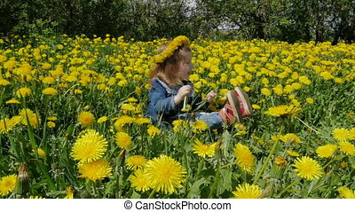 A beautiful, cheerful girl sits in dandelions. Children and...