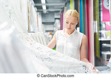 Woman choosing the right item for her apartment in a modern...