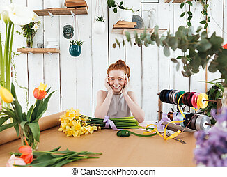 Smiling woman florist holding her head loooking camera -...