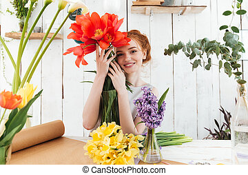 Redhead lady florist looking camera and smiling while...