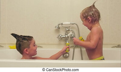 Two little boys having fun while taking bath in bathtub