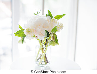 white peony flowers on coffee table in white room interior,...
