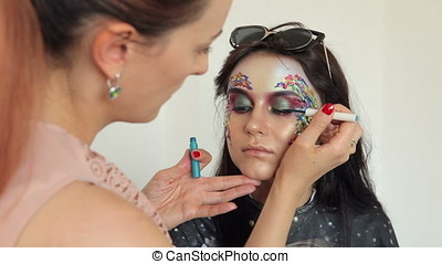 Make up artist applying creative makeup to a model before...