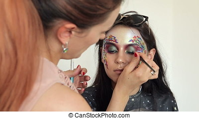 Make up artist working on a model before shooting