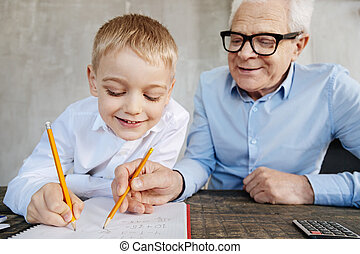 Enthusiastic nice man teaching his grandchild math - Sharing...