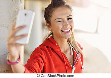 Woman jogging on the beach with smartphone - Picture of...