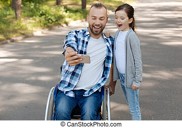 Positive father and daughter looking straight at telephone -...