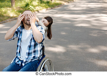 Little female person covering eyes of her father - Play...