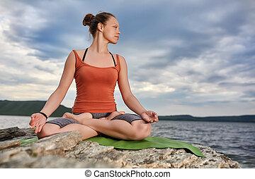 Attractive woman is practicing yoga on the stone near...