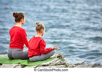 Rear view of young mother and daughter doing yoga exercises...