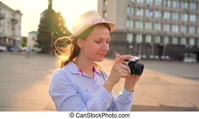Girl is walking around the city and taking photos of sights on a film camera