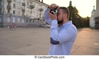 Man is walking around the city and taking photos of sights...