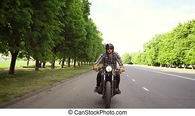 Biker riding a motorcycle on a road surrounded by trees -...