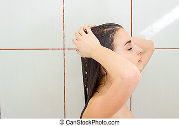 Portrait of a young brunette who is standing under the shower with wet hair