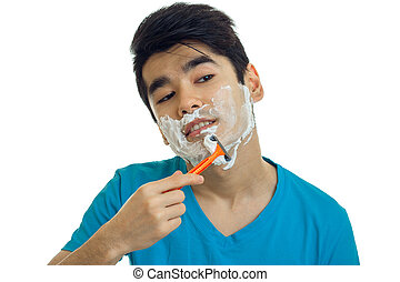 Portrait of a handsome young guy with foam on his face which looks away and shaves his beard