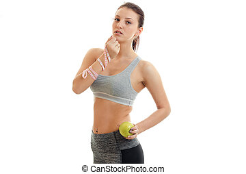 cute slim fitness girl posing in the Studio with an Apple in her hand