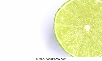 The cut lime slice rotating on a white background.