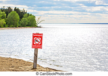 Warning sign on the river - bathing is forbidden, dangerous to life