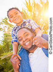 Mixed Race Son and African American Father Playing Piggyback Outdoors Together.