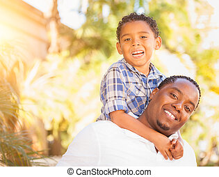 Mixed Race Son and African American Father Playing Outdoors...