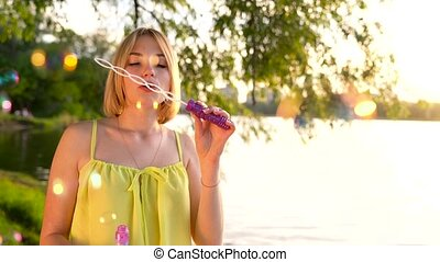 Young beautiful blonde blowing soap bubbles outdoors - slow...