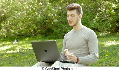 handsome guy talking on the video via laptop in the Park and...